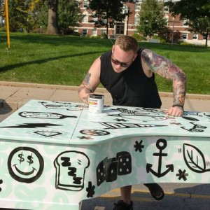 Van Holmgren, a Des Moines artist and volunteer for City Sounds: the Des Moines Public Piano Project paints a grand piano in 2014. (Photo: The Des Moines Register)