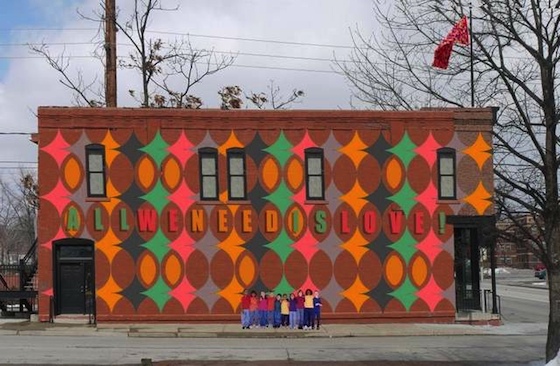 """A proposed design with rhombus [or diamond] pattern is superimposed over an image of the building.  The words """"All We Need Is Love"""" (inspired by the 1967 song """"All You Need Is Love"""" written by John Lennon) is included in the design."""