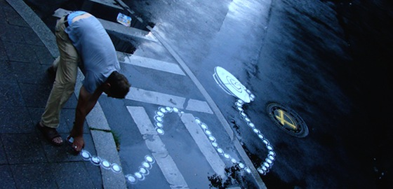 """Peter Gibson, aka Roadsworth,  began to play with the language of the streets, overlaying city asphalt markings with his own images: a crosswalk became a giant boot print, vines choked up traffic dividers, and electrical plugs filled parking spots. His art poses the question, """"Who owns public space?"""" Roadworth's expressive commentary on traffic, US oil dependency and how people move throughout the city has earned him acclaim internationally."""