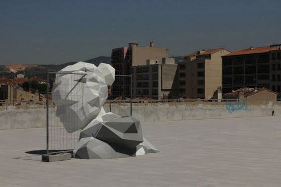 Artist David Mesquich has realized a monumental on-site sculpture of a female head, geometrically abstracted to be a polygonal form. Made of recycled plastic,'pressure' was folded into its final shape, then intertwined with a gated fence. The model's prismatic structure refracts light and casts dramatic shadows on its surroundings.