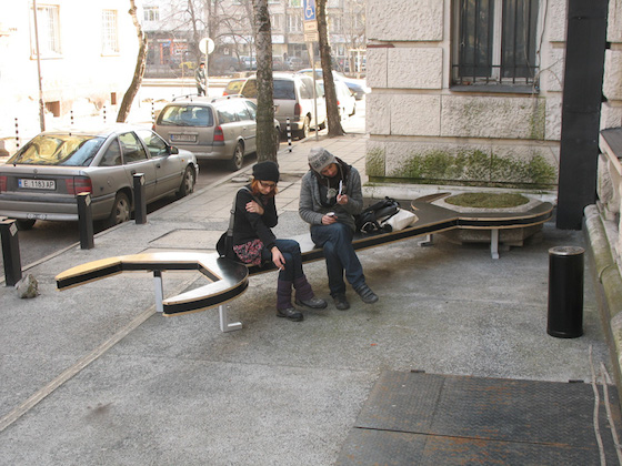 """In another project, the Transformers built a """"wrench bench"""" with ends designed to fit precisely around the large hexagonal flower pots that dot the city and resemble giant concrete screws."""