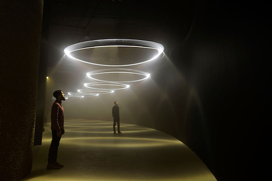 Visitors enjoy the 'United Visual Artists: Momentum' installation at The Curve at the Barbican Centre on February 12, 2014 in London, England. The installation consists of 12 pendulums suspended overhead along the 90m length of the Curve. Each pendulum projects a horizontal plane of light, plus a vertical spotlight on a darkened environment filled with water-based smoke. Photo: Bethany Clarke