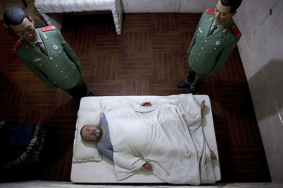 Pictured is one of the most powerful scenes that illustrates the prisoner's physical vulnerability. —Looking down, the viewer sees Ai Weiwei covered by a blanket, lying flat on his back, with two guards standing just a few inches away from the cot and guarding him all night long as he sleeps.