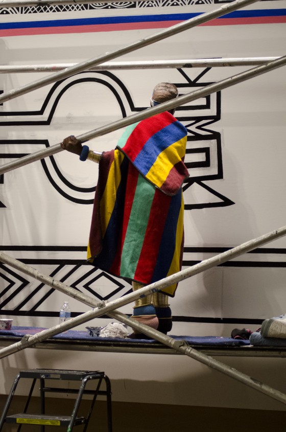Esther leans from scaffolding as she continues work on a design. September 2014. Photo by Will Solis for Richmond Arts Review, 8 October 2014.