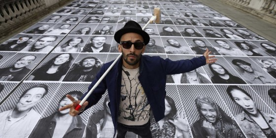 "French artist JR poses with his public art installation ""Actions"" on the Terrace at Somerset House in London on October 7, 2013."