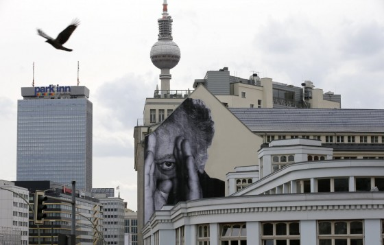 "For ""Wrinkles of the City,"" JR's plastered murals of the elderly around various cities. In this photo, a bird flies past Berlin's decorated television tower."