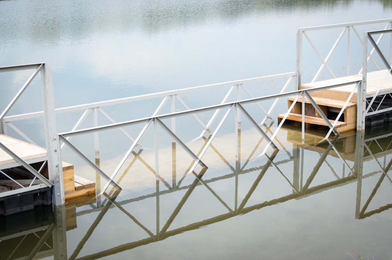 """Detail of """"Wading Bridge"""" in tranquil waters of Copper Creek Lake in Pleasant Hill, Iowa."""