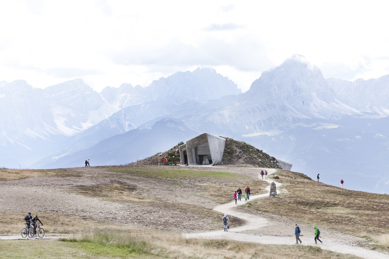 The Messner Mountain Museum is in Corones, Italy. The museum is arranged over several levels to reduce its footprint. A series of staircases, like waterfalls in a mountain stream, cascade within the museum to connect the exhibition spaces and describe the circulation over three levels. The wide windows allow natural light to penetrate deep within the museum, drawing visitors forward throughout the interior to emerge at the viewing terrace which cantilevers 6 meters from the mountain wall over the valley below. In this view, the entrance appears to erupt from the rock and will be overgrown with greenery.