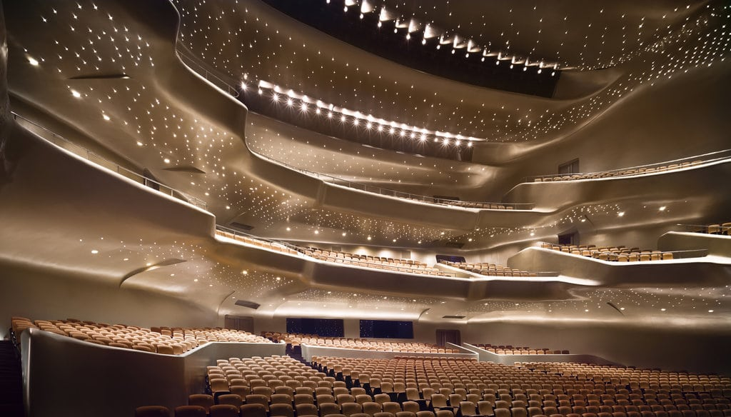 Guangzhou Opera House's fluid forms — which have been compared to a cluster of rocks in a riverbed, their surfaces eroded by the water's currents — give sudden focus to the energy around it so that you see the whole area with fresh eyes. The opera house is located in Guangdong province, People's Republic of China.