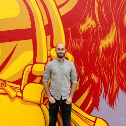 Artist Nick Goettling in front of some of his past artwork. Photo courtesy of Downtown Issaquah Association